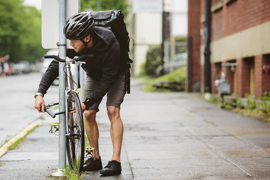 Man parking bicycle by pole while standing on wet footpath