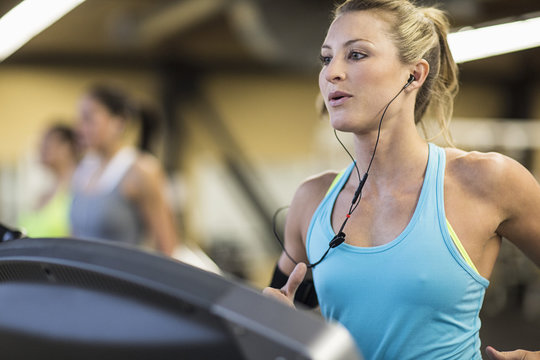 Woman looking away while exercising on treadmill in gym