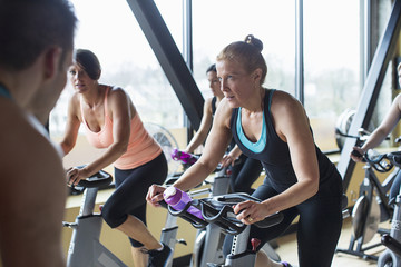 Male instructor guiding women cycling on exercise bikes at gym