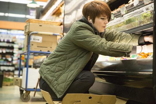 Side view of female worker arranging food at supermarket