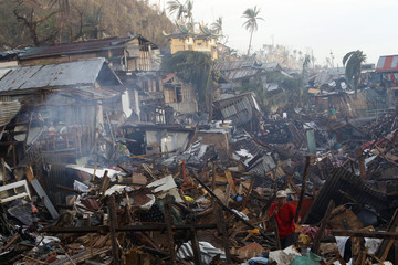 A man salvages debris as he rebuilds his community after the Super typhoon Haiyan battered Tacloban city