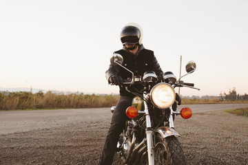 Male biker sitting on motorcycle by road against clear sky during sunset