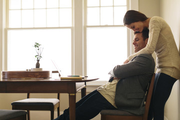 Side view of woman embracing man sitting on chair at home