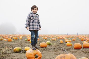 Portrait of boy standing on pumpkin at farm during foggy weather