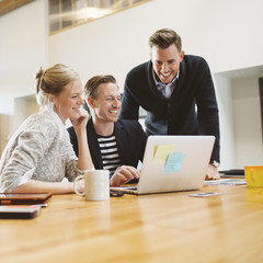 Smiling colleagues looking at laptop in office