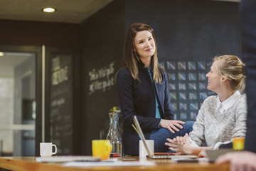 Female colleagues talking while sitting at table in office