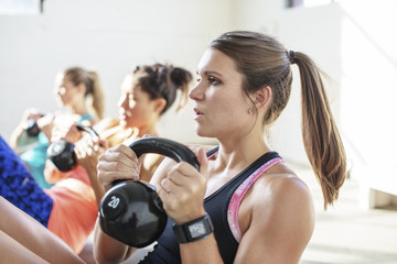 Female athletes lifting kettlebells in gym