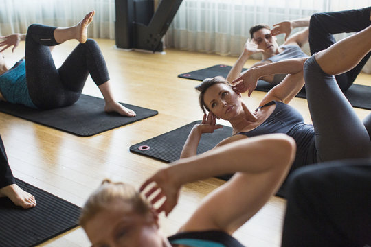 High angle view of male instructor with women exercising on exercise mats in gym