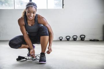 Smiling female athlete tying shoelace in gym