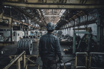 Rear view of male worker standing in factory