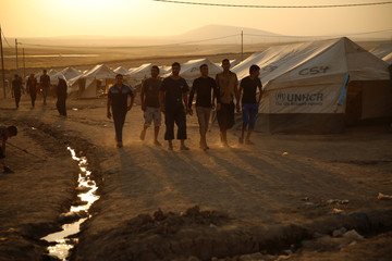 Iraqi refugees, who fled from the violence in Mosul, walk during sunset inside the Khazer refugee camp