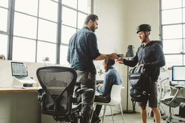 Businessman giving equipment to colleague in creative office