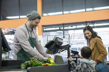Worker making bill while standing with customer at counter in supermarket