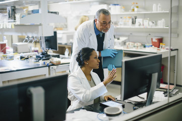 Female doctor discussing with male doctor in medical room seen through glass