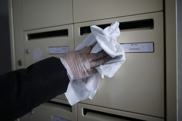 """A service agent cleans the letter box with the name reading """"Clain Fabien"""" is seen at the entrance of an apartment building where Fabien Clain grew up in Alencon"""