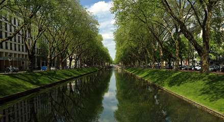 Panorama summer bright view of the historic trade avenue Koenigsallee (King's Avenue) Germany with canal in the middle, Dusseldorf, Germany