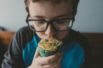 Close-up of boy eating cupcake at home