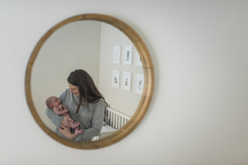Mother and son reflecting on mirror at home
