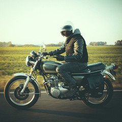 Portrait of male biker gesturing while riding motorcycle on country road against sky