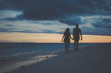 Silhouette couple holding hands and walking at beach during sunset