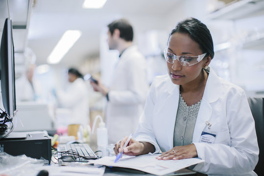 Female doctor working at desk with coworkers in background