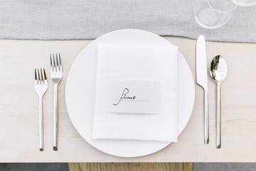 Overhead view of silverware by plate with text on dinning table