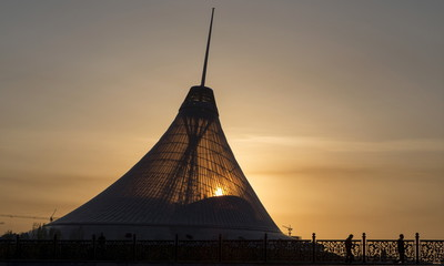 People are silhouetted as they walk during sunset in front of the Khan Shatyr Shopping and Entertainment Center in Astana