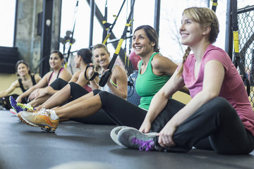 Female friends relaxing while sitting by resistance bands in gym