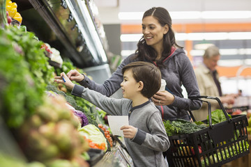 Mother and son shopping for vegetables at supermarket