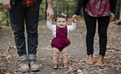 Portrait of baby girl holding parents hands while standing at forest