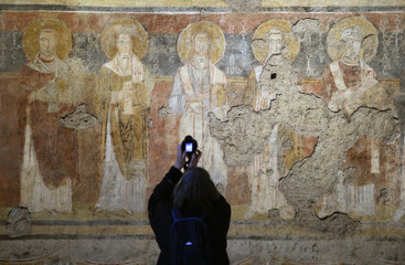 A visitor takes pictures of frescoes inside the sixth-century Santa Maria Antiqua church in Rome