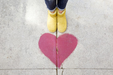 Low section of person standing by red heart shape on footpath