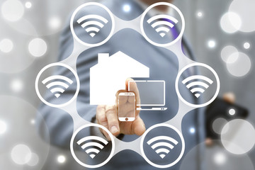 Smart House Concept. Internet of things (IoT). Business man presses IOT solution represented by symbol connected with icons of typical IoT. Intelligent home management. Control with Wi Fi.