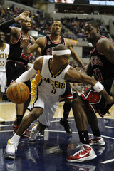 Indiana's T.J. Ford gets past three Bulls players during an NBA basketball game in Indianapolis