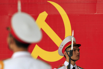 Military soldiers stand guard in front of the symbol of Vietnam's Communist Party during a ceremony to mark the 85th anniversary of its foundation in Hanoi