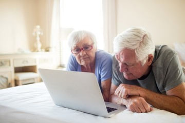 Senior couple using laptop on bed in bedroom