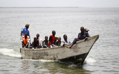 Volunteers and Ugandan government authorities sail in a boat carrying the bodies of people killed after a boat carrying mostly Congolese refugees capsized at the shores of Lake Albert in Ntoroko district in Western Uganda