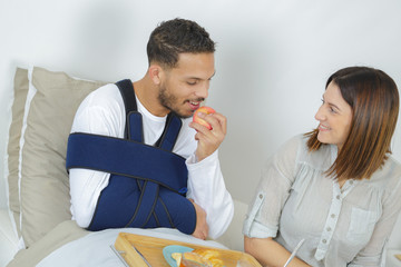 Injured man eating apple with left hand