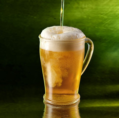 A glass of beer on a green background.