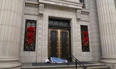 A homeless man sleeps at the doorway of a PNC Bank branch, one block from the White House, in Washington