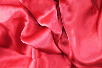 Red fabric background texture wave. Pink silk fabric close-up with an overflow of light and a delicate contrast. Symbol of love, sex, passion, tenderness