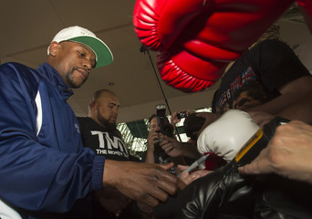 Undefeated welterweight boxer Mayweather Jr. of the U.S. signs boxing gloves for fans as he makes his official arrival at the MGM Grand Hotel & Casino in Las Vegas, Nevada