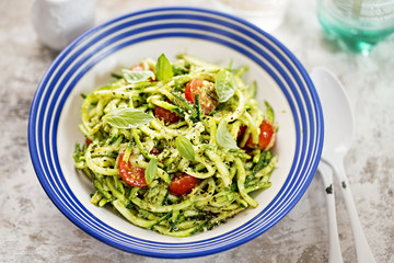 Spiralled courgette spaghetti with green pesto and cherry tomatoes