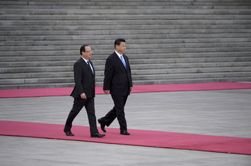 Chinese President Xi Jinping escorts French President Francois Hollande as they prepare to review an honour guard outside the Great Hall of the People in Beijing