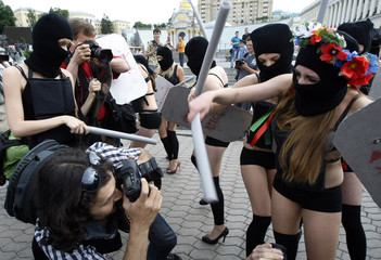 """Activists from the Ukrainian female rights organization """"Femen"""", depicting Interior Ministry officers, stage a mock scuffle with photographers during a rally in Kiev"""