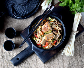 Udon noodles with chicken, pepper, carrots, onions, zucchini and mushrooms in teriyaki sauce. Asian cuisine.