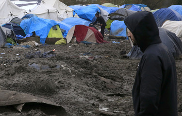 A migrant walks in a muddy field at a camp of makeshift shelters for migrants and asylum-seekers from Iraq, Kurdistan, Iran and Syria, called the Grande-Synthe jungle, near Dunkerque