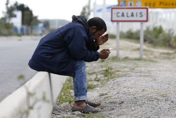 A migrant looks at his mobile phone as he sits near a road sign on the main access route to the Ferry harbour Terminal in Calais, northern France