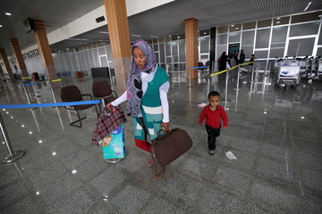 A woman and her child head back home after hearing that an evacuation flight was cancelled at Sanaa airport