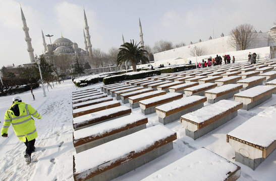 A police officer walks in the snow covered Sultanahmet square with the Ottoman-era Sultanahmet Mosque in the background in Istanbul